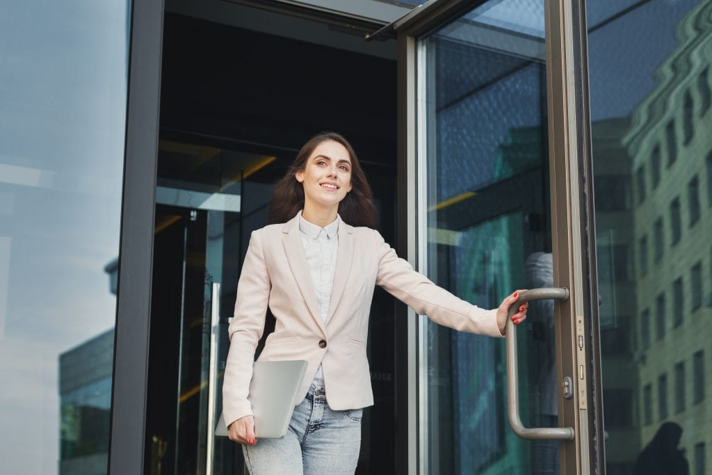 Young Businesswoman walking out of building
