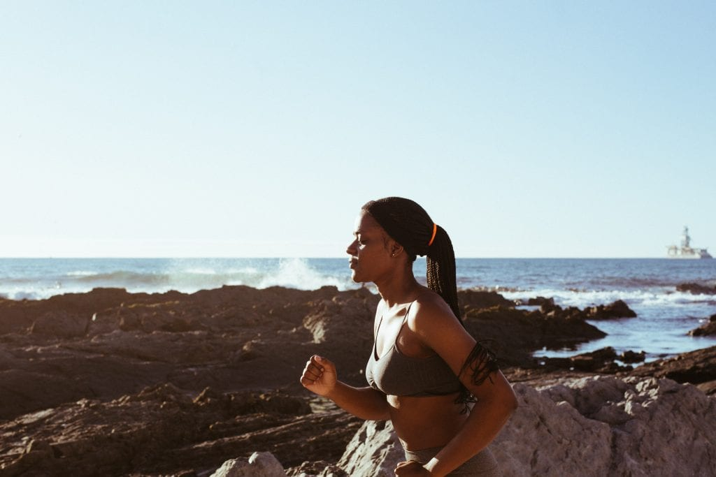 Young woman running along coastline